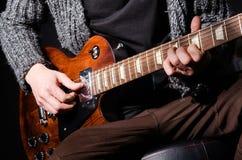 Hombre que toca la guitarra en sitio oscuro Imágenes de archivo libres de regalías