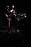 Hombre que toca la guitarra en sitio oscuro Foto de archivo libre de regalías