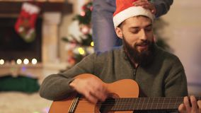 Hombre que toca la guitarra y que canta la sentada en el piso cerca de árbol del Año Nuevo en sitio moderno Mujer con la guirnald almacen de metraje de vídeo