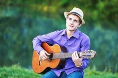 Hombre que toca las seis guitarras acústica de la secuencia Imágenes de archivo libres de regalías