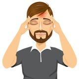 Hombre que toca sus templos que sufren un dolor de cabeza Foto de archivo libre de regalías