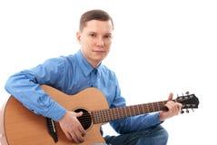Hombre que toca una guitarra acústica Imagen de archivo libre de regalías