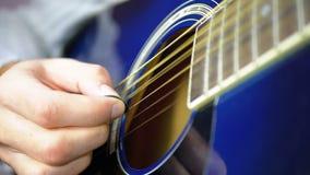 Hombre que toca una guitarra acústica con un mediador Cámara lenta almacen de video