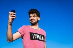Hombre que toma el autorretrato con el teléfono elegante Fotos de archivo libres de regalías