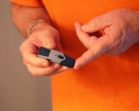 Hombre que toma el azúcar de sangre con el dispositivo Foto de archivo libre de regalías