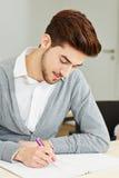Hombre que toma el examen en universidad imagen de archivo