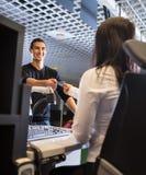 Hombre que toma el pasaporte del personal femenino en el enregistramiento del aeropuerto Imagen de archivo