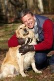 Hombre que toma el perro en paseo a través de Autumn Woods Imagen de archivo