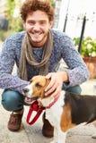 Hombre que toma el perro para el paseo en la calle de la ciudad Fotos de archivo libres de regalías