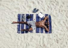 Hombre que toma el sol en la playa Fotografía de archivo