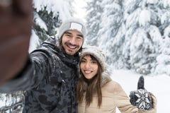 Hombre que toma a foto de Selfie la nieve romántica joven Forest Outdoor de la sonrisa de los pares Imagen de archivo