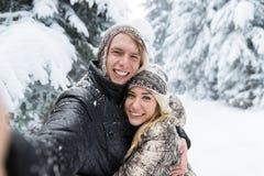Hombre que toma a foto de Selfie la nieve romántica joven Forest Outdoor de la sonrisa de los pares Fotografía de archivo