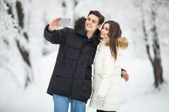 Hombre que toma a foto de Selfie la nieve romántica joven Forest Outdoor Winter Pine Woods de la sonrisa de los pares Los pares h Imagen de archivo libre de regalías