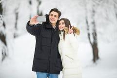 Hombre que toma a foto de Selfie la nieve romántica joven Forest Outdoor Winter Pine Woods de la sonrisa de los pares Los pares h Fotos de archivo