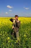 Hombre que toma imágenes en campos de flores amarillos Fotografía de archivo libre de regalías