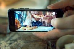 Hombre que toma la foto de una muchacha que come la pizza imagenes de archivo