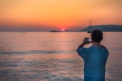 Hombre que toma la imagen con el teléfono móvil en la puesta del sol, Croacia fotografía de archivo libre de regalías