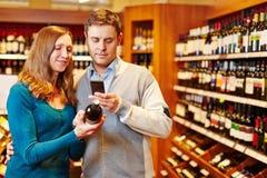 Hombre que toma la imagen de la botella de vino en supermercado Imagenes de archivo