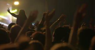 Hombre que toma las fotos del concierto en Smartphone almacen de metraje de vídeo