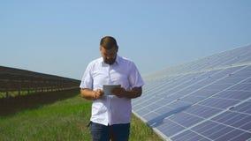 Hombre que toma notas en la tableta en una planta de energía solar almacen de video