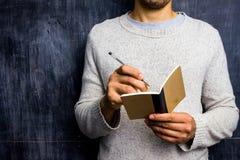 Hombre que toma notas por la pizarra Fotos de archivo libres de regalías