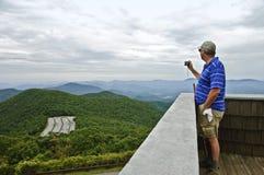 Hombre que toma un cuadro de montañas imagenes de archivo