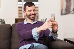 Hombre que toma un selfie en casa Imagen de archivo