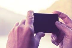 Hombre que toma una foto con su teléfono Imagen de archivo