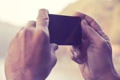 Hombre que toma una foto con su teléfono Foto de archivo libre de regalías