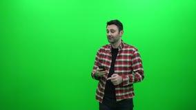 Hombre que toma una foto de Selfie con su Smartphone en una pantalla verde almacen de metraje de vídeo