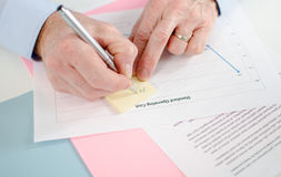 Hombre que toma una nota sobre un post-it Imagen de archivo libre de regalías