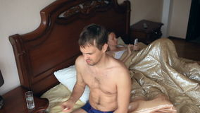 Hombre que toma una píldora antes de sexo Una mujer está esperando a un hombre en cama almacen de video