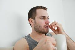 Hombre que toma una píldora Fotografía de archivo libre de regalías