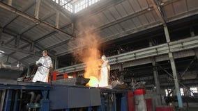 Hombre que trabaja con el metal líquido en fábrica La fábrica del metal chispea almacen de video