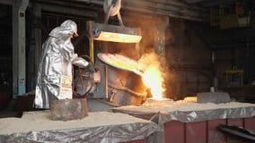 Hombre que trabaja con el metal líquido en fábrica La fábrica del metal chispea metrajes
