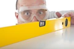 Hombre que trabaja con el nivel de burbuja de aire Fotografía de archivo libre de regalías