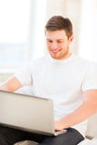 Hombre que trabaja con el ordenador portátil en casa Fotos de archivo