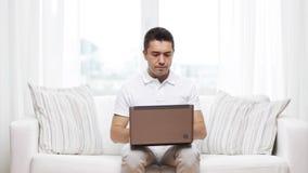 Hombre que trabaja con el ordenador portátil en casa metrajes