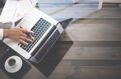 Hombre que trabaja con el ordenador portátil en la oficina soleada Cuaderno moderno, taza de café sólo en la tabla de madera Refl Fotos de archivo libres de regalías