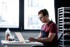 Hombre que trabaja con el ordenador portátil en la panadería Foto de archivo libre de regalías