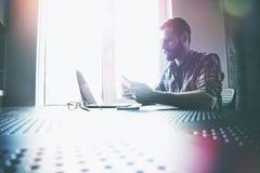 Hombre que trabaja con el ordenador portátil y la tableta digital Imagen de archivo