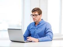 Hombre que trabaja con el ordenador portátil en casa Fotografía de archivo libre de regalías