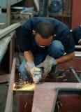 Hombre que trabaja con la amoladora de ángulo Fotos de archivo libres de regalías