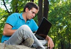 Hombre que trabaja con la computadora portátil en el parque Fotos de archivo libres de regalías