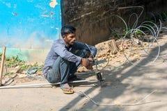 Hombre que trabaja con los alambres eléctricos sin los engranajes de la seguridad que llevan fotos de archivo