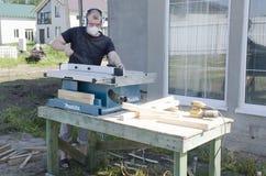 Hombre que trabaja con madera de pino en aserrar la tabla circular Makita foto de archivo libre de regalías