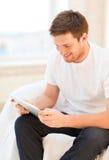 Hombre que trabaja con PC de la tableta en casa Imagen de archivo