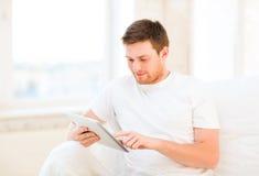 Hombre que trabaja con PC de la tableta en casa Imagenes de archivo