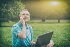 Hombre que trabaja con su ordenador portátil en el parque imagenes de archivo