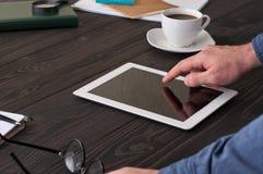 Hombre que trabaja en casa usando la tableta Foto de archivo libre de regalías